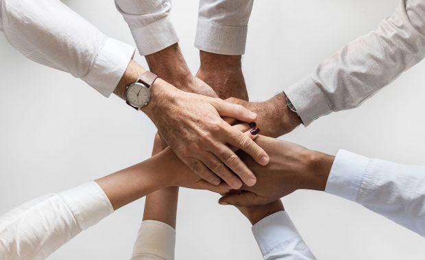 viele übereinander liegende Hände als Symbol für Teamspirit